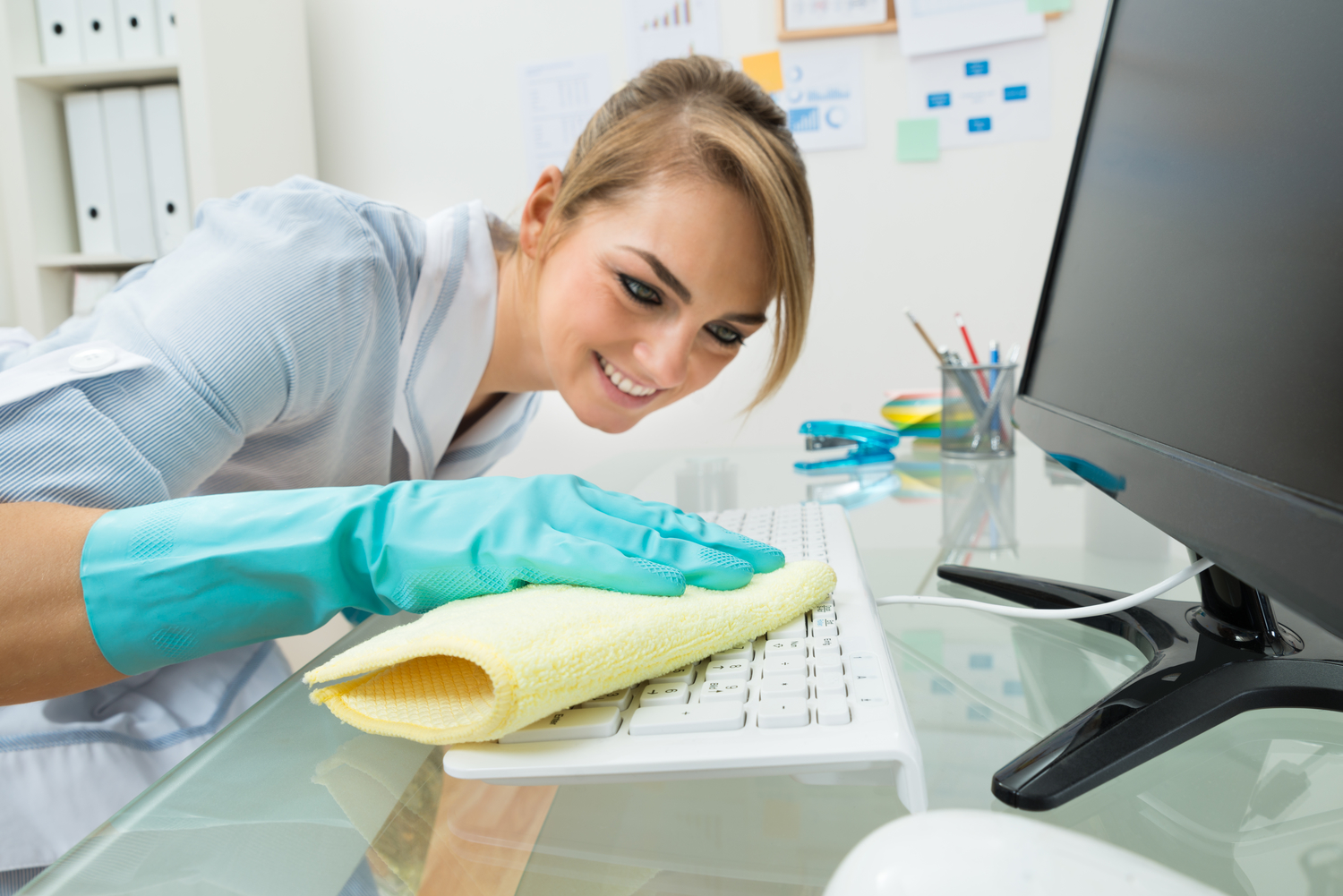 Maid Cleaning Keyboard At Desk